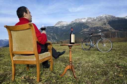 uomo in pausa con bicchiere di vino in mezzo ad un prato